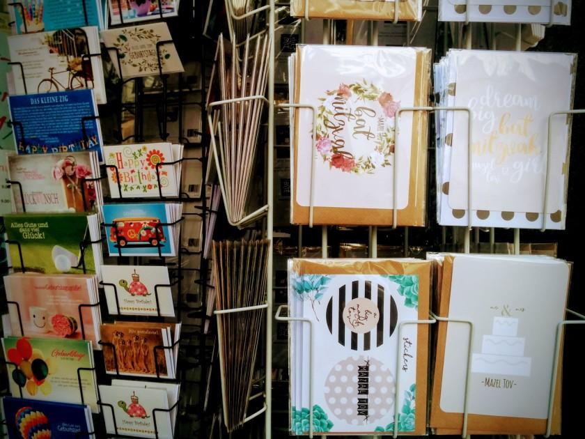 Ständer mit jüdischen Glückwunschkarten neben Ständer mit nichtjüdischen Glückwunschkarten.