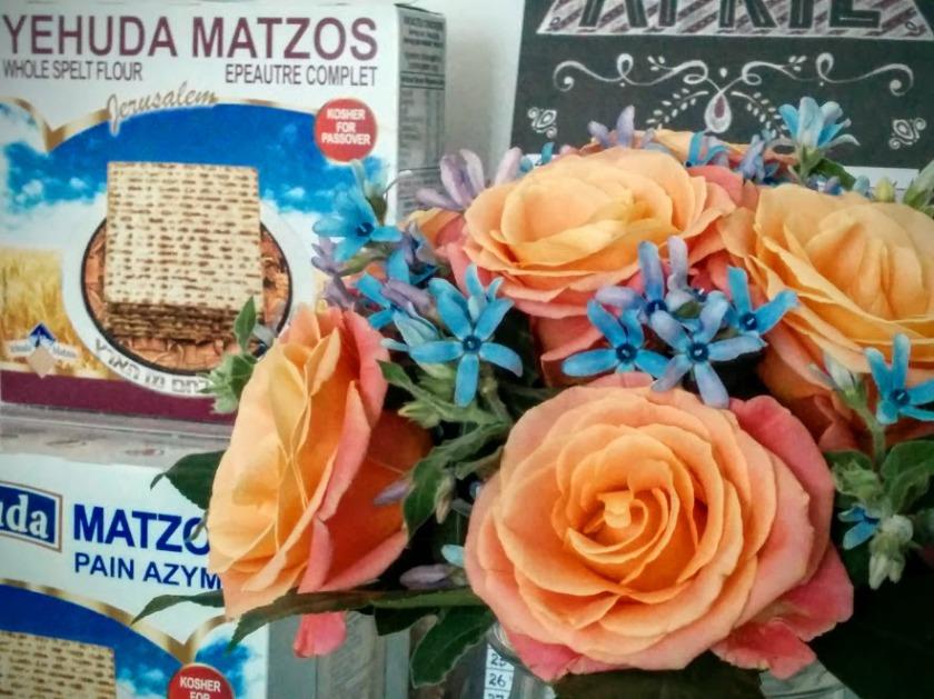 Blumenstrauß vor Matzot-Packungen.