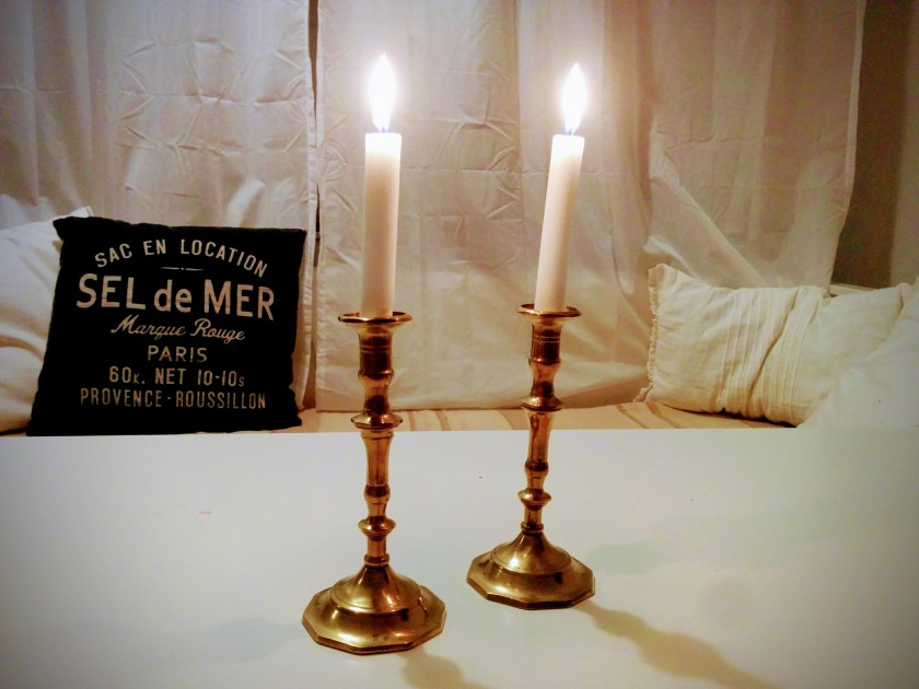 Zwei brennende Kerzen in Messingleuchtern