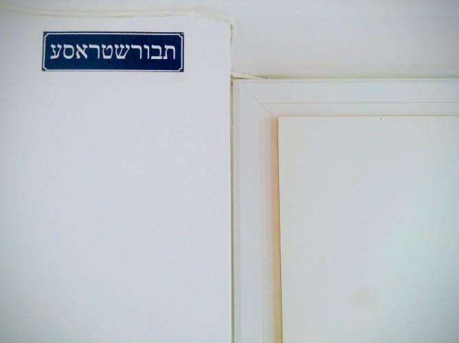 """Schild im Stil der Wiener Straßenschilder, auf dem in jiddischen Lettern """"Taborstraße"""" steht"""