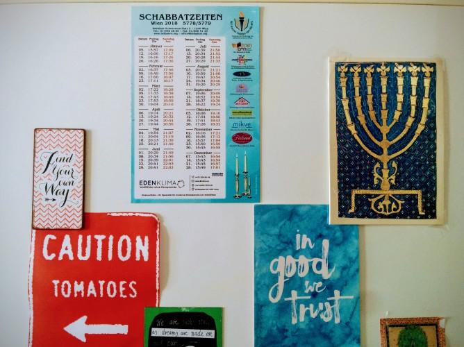 """Kühlschranktür mit verschiedenen Aufklebern, darunter ein Bild einer Menorah und ein Kalender für Schabbat-Zeiten. Außerdem ein Schild """"Caution Tomatoes""""."""