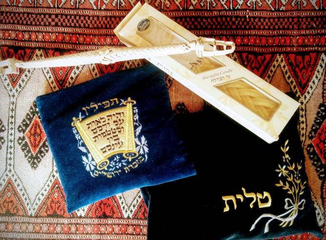 Zwei in Samttaschen verpackte Tallitot, eine Havdalah-Kerze und ein Besamim-Gebinde.