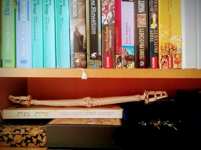 Tallitot, Besamim-Gebinde und Havdalah-Kerze verstaut unter eine Reihe von Büchern von J.R.R. Tolkien und Terry Pratchett.