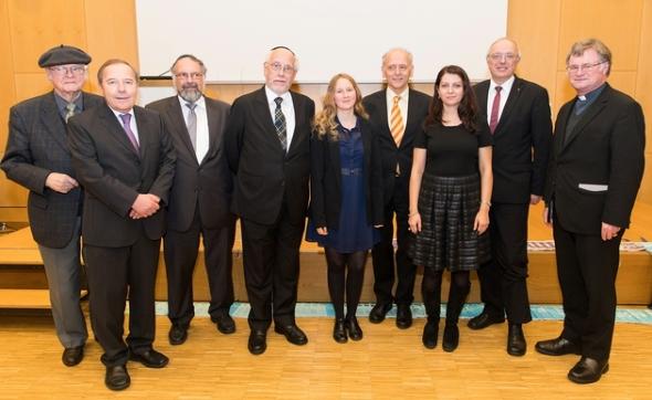 Zwischen acht Männern, religiöse Vertreter, stehen Muna Duzdar und ich.