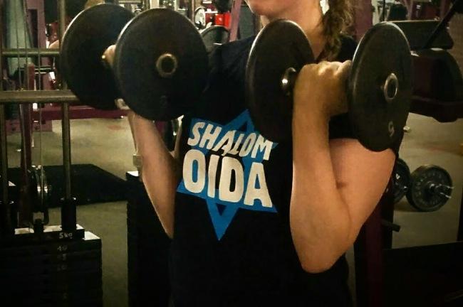 """Junge Frau mit einem T-Shirt, auf dem """"Shalmon, Oida!"""" steht, hebt schwere Kurzhanteln"""