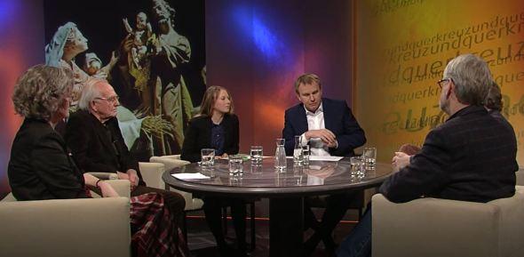 sechs Personen an einem runden Tisch in einem Fernsehstudio, davon zwei Frauen